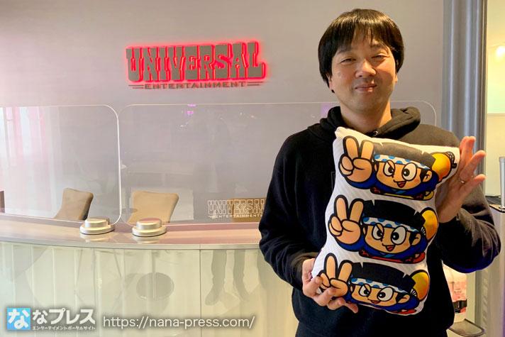 ユニバ本社でドンちゃんグッズを持つ小野P